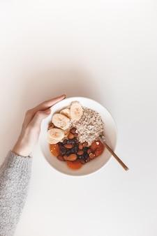 Carboidrati prima colazione sana. farina d'avena con frutta secca su un piatto bianco. vista dall'alto