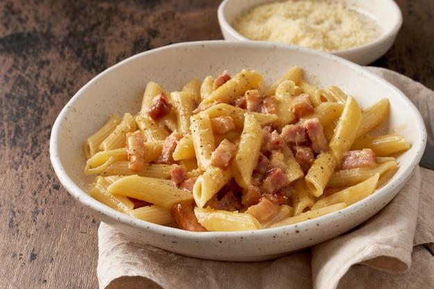 Pasta alla carbonara. penne con pancetta, uovo, parmigiano e salsa di panna
