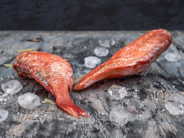 Carcasse di branzino congelato per uno sfondo scuro per preparare un pranzo sano da vicino