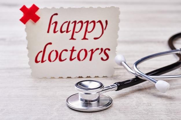 Biglietto per la festa del dottore. stetoscopio su superficie di legno grigia.