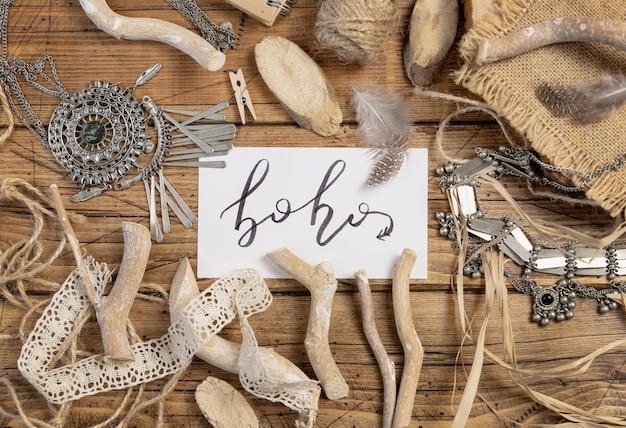 Biglietto con il testo scritto a mano boho con decorazioni bohémien intorno alla vista dall'alto su un tavolo di legno