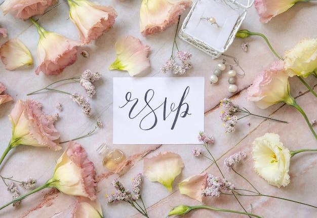 Biglietto con il testo scritto a mano rsvp circondato da fiori rosa, orecchini, anello di fidanzamento, petali e flacone di profumo intorno alla vista dall'alto su un tavolo di marmo. concetto romantico