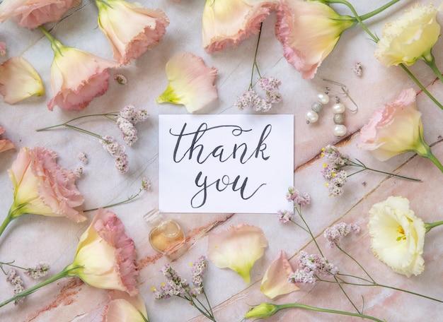 Biglietto con il testo scritto a mano grazie circondato da fiori rosa, orecchini, petali e flacone di profumo intorno alla vista dall'alto su un tavolo di marmo. concetto romantico