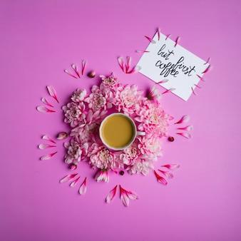 Carta con iscrizione ma primo caffè, caffè in una tazza con fiori di crisantemo intorno.
