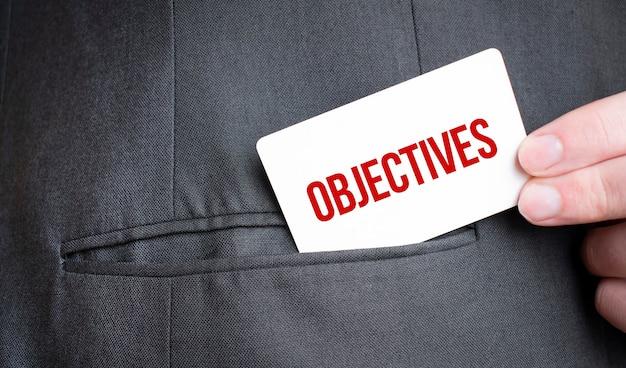 Scheda con testo di obiettivi in tasca del vestito dell'uomo d'affari. concetto di affari di investimento e decisioni.
