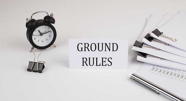 Scheda con testo regole di base su uno sfondo bianco, vicino a forniture per ufficio e sveglia. concetto di affari.