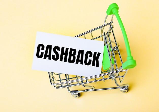 La carta con la parola cashback è nel carrello. concetto di mercato.