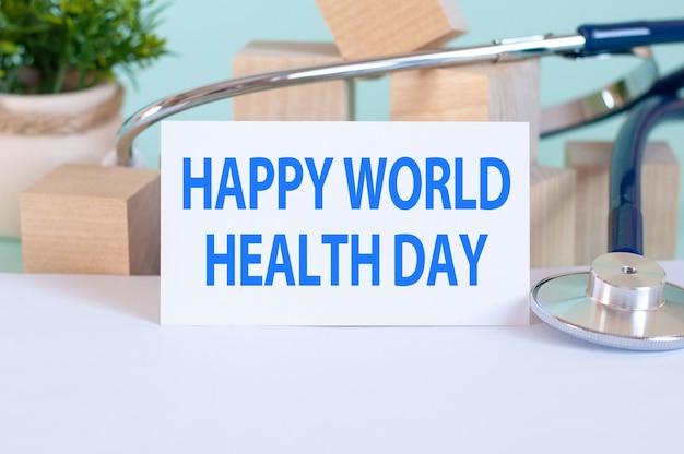 Scheda con le parole checkup medico, stetoscopio, blocchi di legno e fiori sul tavolo