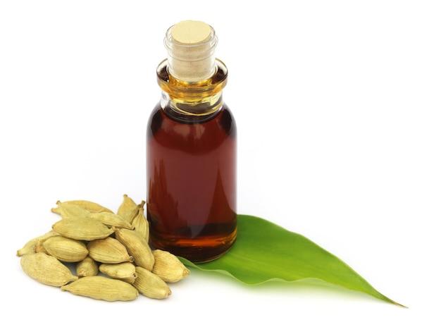 Cardamoni e foglie con olio essenziale su sfondo bianco