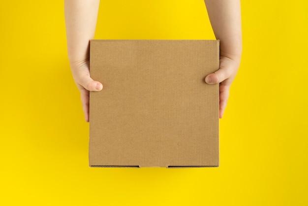 Scatola di cartone nelle mani dei bambini su sfondo giallo Foto Premium
