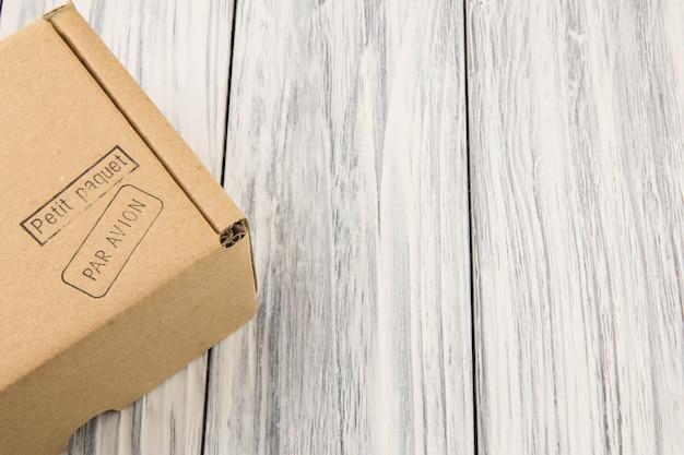 Scatola di cartone isolata sulla tavola di legno bianca