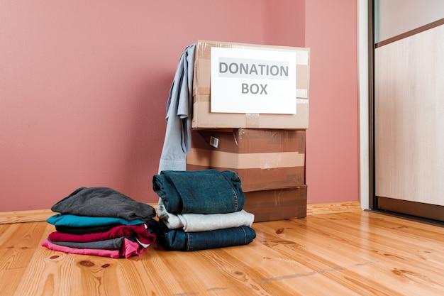 Scatola di cartone con vestiti di donazione e diversi oggetti su legno, concetto di donazione