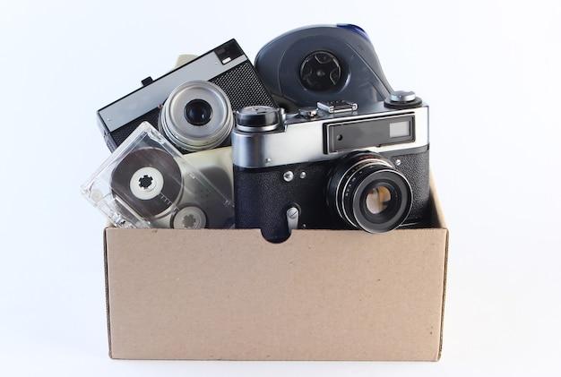 Scatola di cartone con fotocamera a pellicola retrò, cassetta audio, gamepad su un bianco