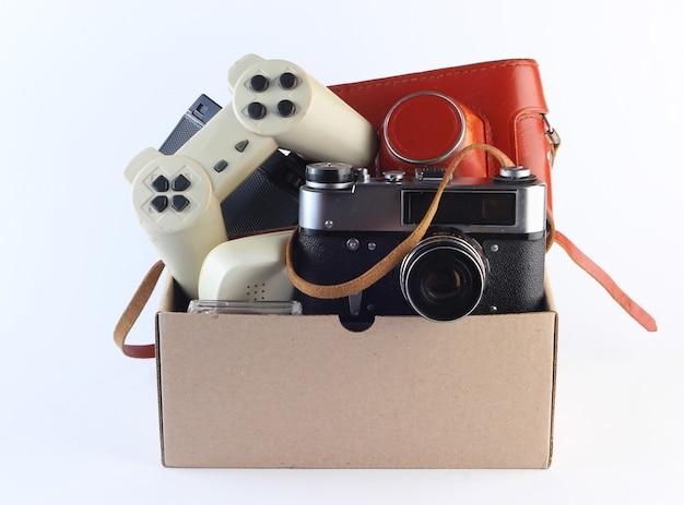 Scatola di cartone con fotocamera a pellicola retrò, gamepad su un bianco.