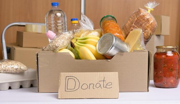 Scatola di cartone con vari prodotti, frutta, pasta, olio di semi di girasole in bottiglia di plastica e conservazione. concetto di donazione