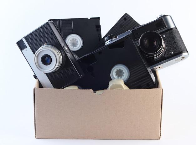 Scatola di cartone con videocassette e fotocamera a pellicola retrò su un bianco. oggetti d'antiquariato, spazzatura