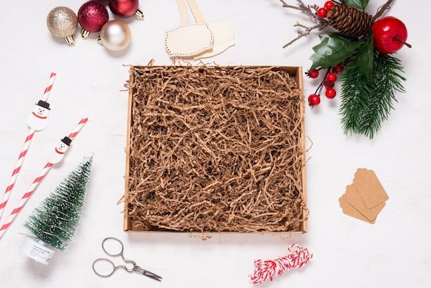 Scatola di cartone su scrivania in legno decorata con ornamenti natalizi