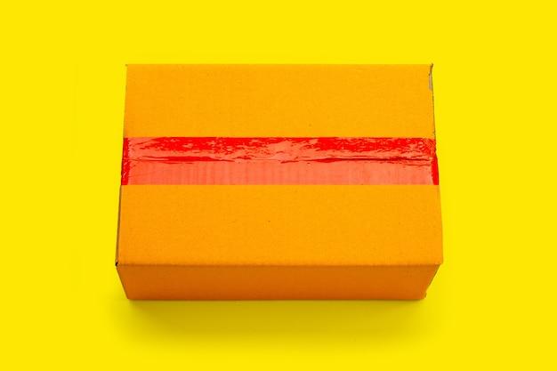 Scatola di cartone su sfondo giallo.