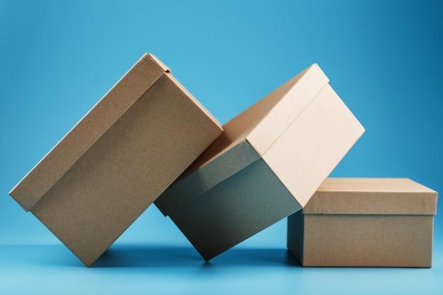 Scatole di cartone sparse su uno sfondo blu, spazio libero.