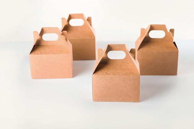 Scatole di cartone su uno spazio bianco. imballaggio ecologico del primo piano di prodotti di carta e dello spazio della copia. contenitori artigianali, imballaggi, scatole, pacchi.