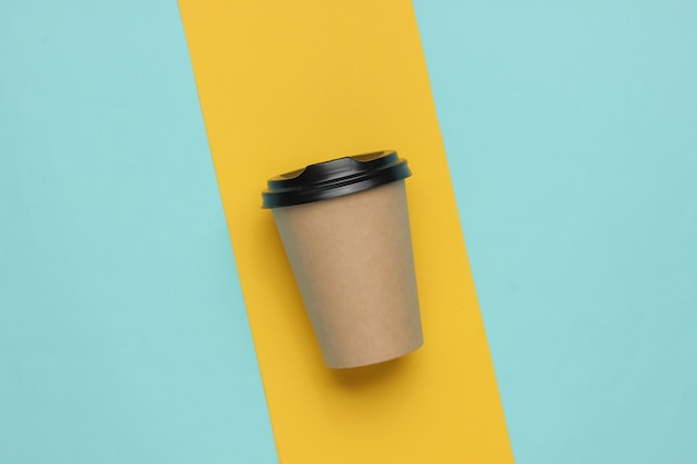 Tazza da caffè in cartone su uno sfondo di carta colorata