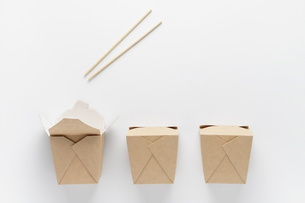 Contenitore di cartone per cibo da asporto e bacchette su sfondo bianco. concetto di consegna fast food.