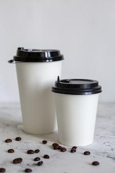 Tazze di caffè in cartone con fagioli