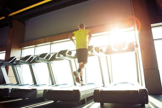 Vista posteriore di allenamento cardio di un uomo atletico maturo in abbigliamento sportivo che corre su un tapis roulant in una palestra