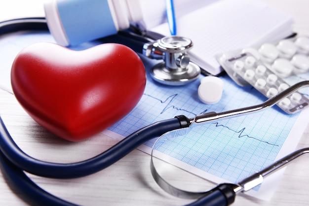 Cardiogramma con stetoscopio e cuore rosso sul tavolo, primo piano