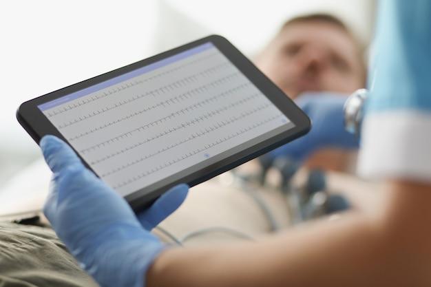 Il cardiologo esamina l'elettrocardiogramma del paziente sul primo piano della compressa