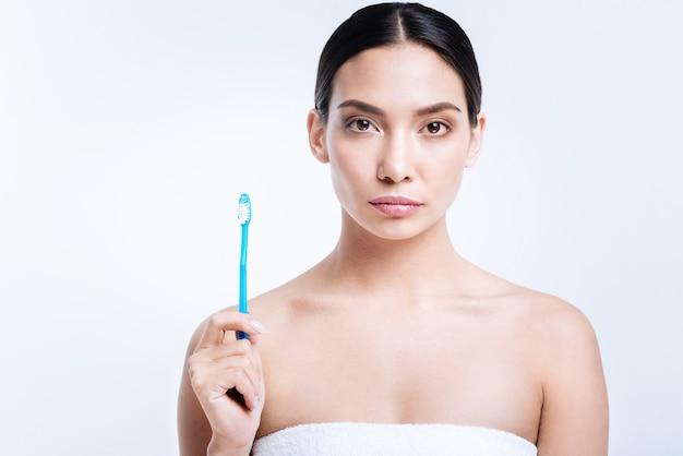 Prenditi cura della salute. bellissima giovane donna con le spalle nude, avvolta in un asciugamano, che mostra il suo spazzolino da denti mentre posa con esso contro un muro bianco