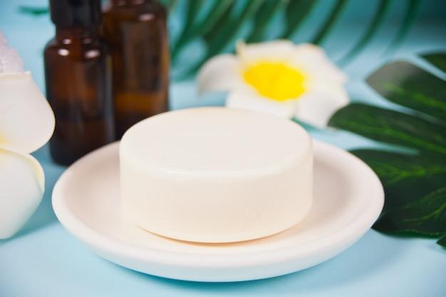 Concetto di cura, bellezza e spa. sapone organico e bottigliette con olii essenziali sotto una foglia di palma.