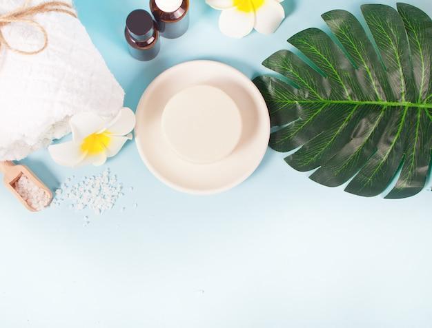 Concetto di cura, bellezza e spa. sapone organico e bottigliette con olii essenziali, asciugamano bianco, foglia di palma. copia spazio. vista dall'alto.