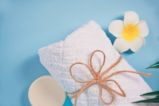 Concetto di cura, bellezza e spa. sapone organico, asciugamano bianco, fiore di plumeria frangipani. copia spazio. vista dall'alto.