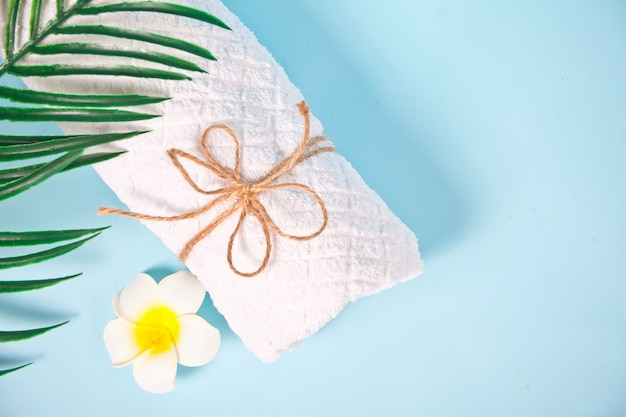 Concetto di cura, bellezza e spa. asciugamano bianco e fiore del frangipane di plumeria. copia spazio. vista dall'alto.