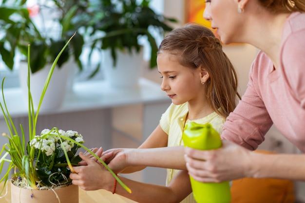 Cura dei fiori. insegnante e studentessa che si prendono cura di bei fiori bianchi alla lezione di ecologia
