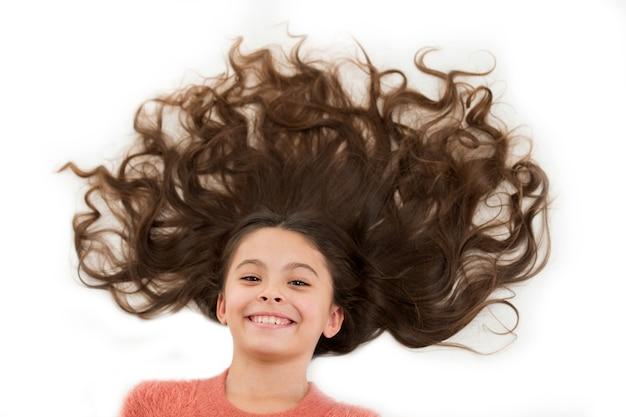 Cura che dona capelli belli e sani. bambino sveglio della ragazza con capelli ricci lunghi isolati su bianco. ricetta maschera per capelli. concetto di salone di parrucchiere. maschera per capelli lunghi. trattamento di bellezza per ricci danneggiati.