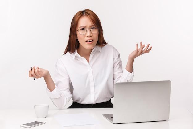 Concetto di imprenditori di carriera, lavoro e donne. ritratto del primo piano della donna di affari asiatica confusa e frustrata che si siede alla scrivania con l'espressione perplessa, chieda perché o cosa, scrollando le spalle perplesso