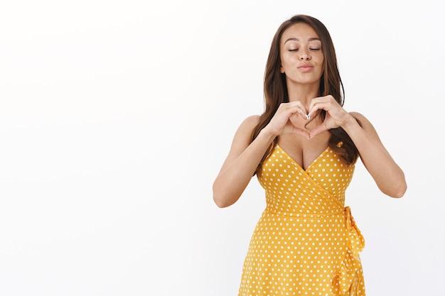 Spensierata e attraente donna civettuola in abito giallo soffia un bacio d'aria con gli occhi chiusi e un romantico sorriso sensuale, mostra il segno del cuore, confessa l'amore, prova un affetto commovente verso il fidanzato
