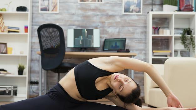 Donna caucasica spensierata che raggiunge per il suo piede nella posa di yoga.