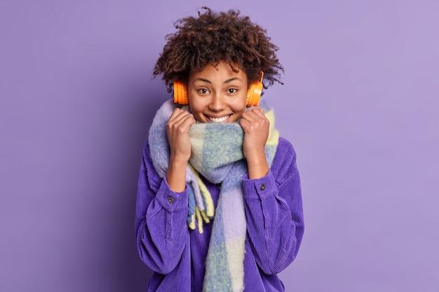 La donna spensierata dalla pelle scura con i capelli ricci indossa una sciarpa calda intorno al collo abiti per il clima freddo utilizza cuffie wireless per ascoltare musica mentre si cammina
