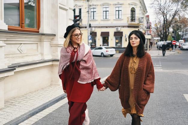 Modelli di donne alla moda spensierate in eleganti abiti autunnali e occhiali. moda giovane ragazze in vestiti di lana intrecciata alla moda e cappelli sulla città urbana, ritratto di autunno.