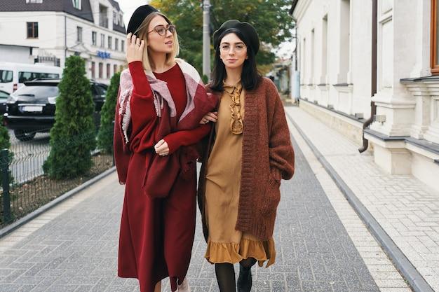Modelli di donne alla moda spensierate in eleganti abiti autunnali e occhiali. moda giovane ragazze in vestiti di lana intrecciata alla moda e cappelli sulla strada urbana della città, ritratto di autunno.