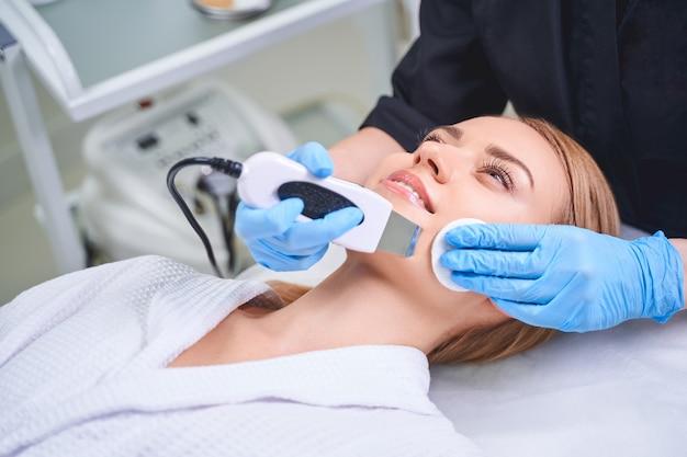 La donna spensierata è sdraiata sul divano mentre si fa sbucciare il viso con un dispositivo ad ultrasuoni dal cosmetologo