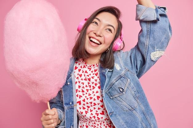 La donna asiatica felice e spensierata si diverte a ballare nel tempo libero e gode di musica preferita in cuffie stereo indossa giacca di jeans sorride alza ampiamente il braccio tiene zucchero filato sul bastone divertimento