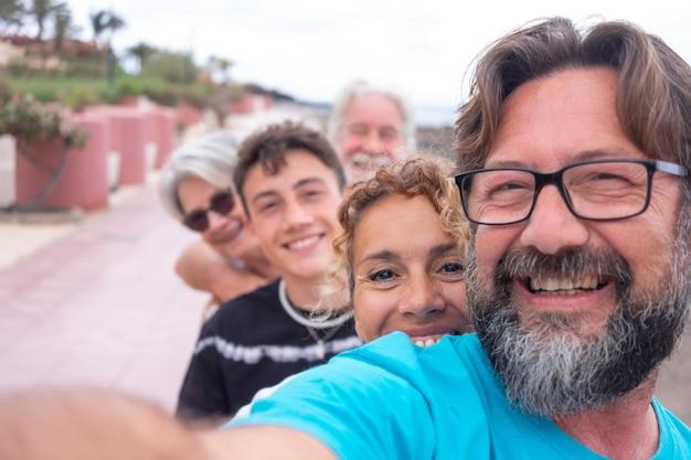 Gruppo spensierato di famiglia multigenerazionale che si fa un selfie all'aperto in spiaggia, guardando la telecamera sorridente