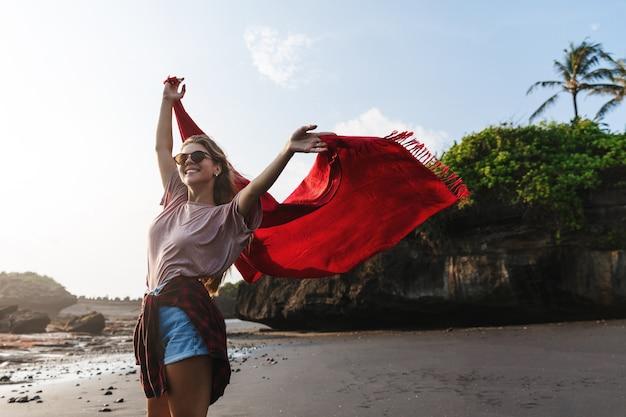 Donna felice spensierata alzando le mani, camminando lungo la spiaggia sabbiosa sull'isola tropicale.