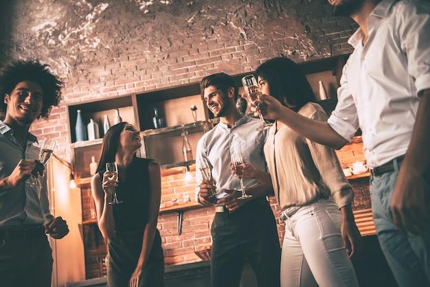 Festa in casa spensierata. inquadratura dal basso di giovani allegri che ballano e bevono mentre si godono la festa a casa in cucina
