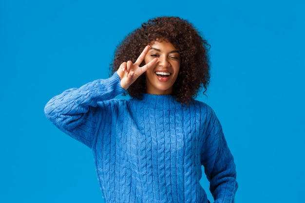 Donna afroamericana adorabile e carismatica spensierata che dice cheeze in posa felice e ottimista, che mostra il segno di pace sopra l'occhio ammiccante e sorridente, che ride felicemente, goditi le vacanze invernali, blu