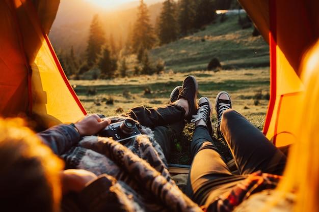 Uomo e donna spensierati durante il viaggio escursionistico autunnale rilassarsi e guardare la natura idilliaca sera nel bellissimo tramonto.